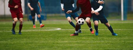 Horizontal picture of soccer match. Soccer football players competing for ball and kick ball during match in the stadium. Footballers in action on soccer league game. Senior level sport competition