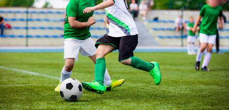 Running Football Soccer Players. Sports Competition Between Youth Soccer Teams. Young Boys in Hard Duel Playing Soccer Game. Junior Footballer Kicking Soccer Ball