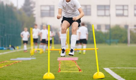 Footballers on Practice Session in Field on Sunny Day. Soccer Player on Fitness Training. Young Soccer Players at Speed and Agility Practice Training Session Standard-Bild