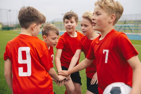 Kids stacking hands in Sports Team. Boys Sports Team Hands Stacked. Kids Sports Soccer Players in a Circle Gathering Before the Tournament Match