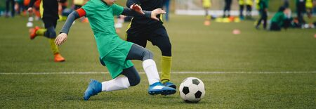 Junior Football Players in a Duel. Players Running Fast After Soccer Ball. School Sports Competetion Between Two Soccer Teams. Soccer Horizontal Background Banco de Imagens