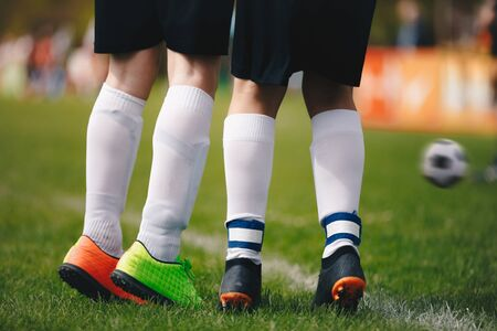 Soccer free kick wall - close up of players legs. Two young football players standing in wall during free kick. Kicked soccer ball in motion in the background. Players jumping up on grass field
