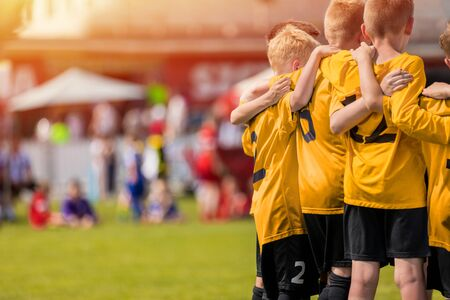 Kids sport team in yellow golden jerseys having pep talk with coach. Children soccer team motivated by trainer. Coaching football youth team. Young boys standing together united Reklamní fotografie