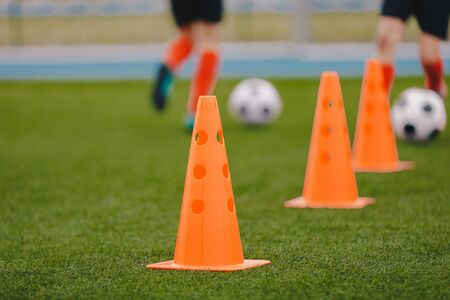 Sports training cones on soccer pitch. Players practice dribbling and passing skills on the grass field. Sports summer camp for young athletes