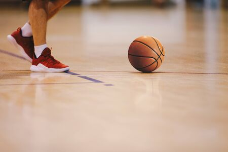 Basketball player walking on wooden court. Basketball over the floor. Basketball sports court Фото со стока