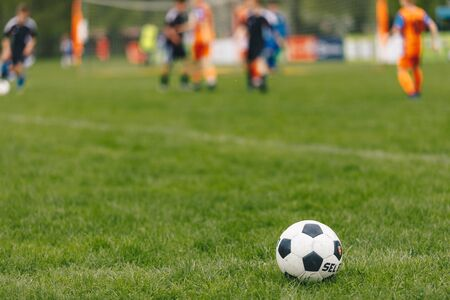 Sports outdoor background. Soccer ball on the field. Football competition tournament match in the blurred background. Sports arena stadium in summer time Фото со стока - 146882988