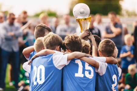 Junior Sport - Celebration. Boys in Sports Soccer Team Rising Up Golden Cup. Young Male Triumphant Footballers. Happy Kids Enjoying Winning in Tournament Stock Photo