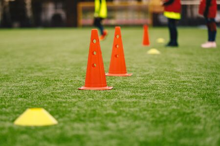 Sports Training Equipment on the Grass Pitch. Soccer Football Cones and Markers. Soccer Junior Players on Training Practice Unit in the Background Stock fotó