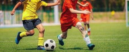 Sporty Football Boys Running After Ball in Duel. School Soccer Competition Between Two Junior Level Players. Multi-ethnic Kids Play Sports