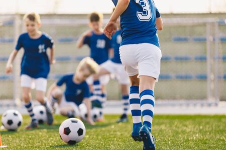 Footballer Running with Ball on Training Pitch. Soccer Skills Training Session. Players Training on the Field. Soccer Obstacle Course. Coaching Soccer Gear Equipment for Field Training