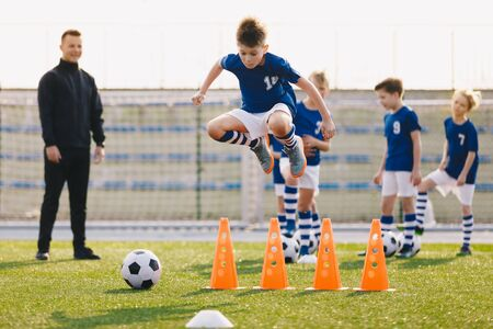 Soccer school training unit. Football boys in team on practice session with youth coach. Player jumping over training cones on the grass field. Speed and agility soccer training Stok Fotoğraf