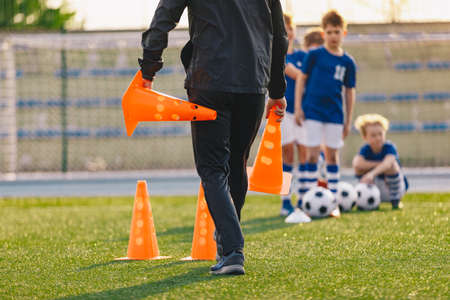 School coach preparing field for soccer training. Kids waiting in line in the background. Trainer holding training cones. Sporst school stadium in the background