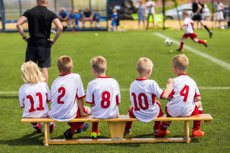 Children Soccer Team Watching Football Match. Children Sport Team in White Shirts. Youth Soccer School Tournament for Children. Young Boys in Soccer Jersey. Football Wooden Bench