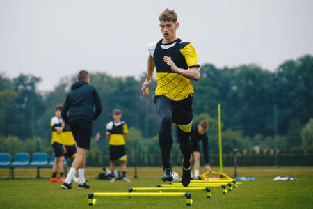 Teenager Boy Soccer Player in Training. Young Soccer Players at Practice Session with Coach. Footballer Jumping Over Hurdles. Boys Running Youth Agility Ladder Drills. Soccer Ladder Exercises Banque d'images