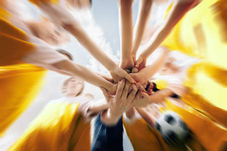 Low angle shot of a group of sports team forming a huddle with their hands. Sports team stacking hands together before the game. Sky with clouds in the background