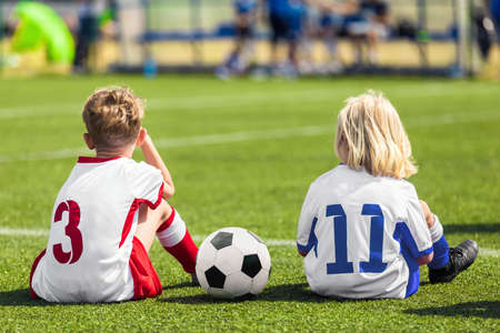 Children players on sports venue. Two school boys sitting on grass soccer field with classic football ball. Two boys from opposite teams watching game. School sports competition Banco de Imagens