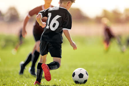 Kids in Soccer Club. Sports Summer Training Camp for School Children. Sports Summer Activity for Junior Level Athletes. Boy Running After Ball on Grass