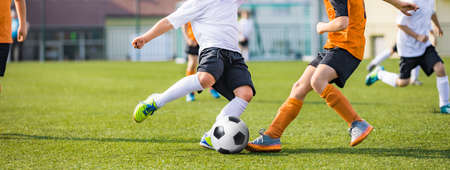 Horizontal Soccer Background. Young Football Players Kicking Ball on Soccer Field. Soccer Horizontal Background. Youth Junior Athletes in Soccer Jersey Shirts