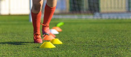 Summer Training Camp. Soccer Drills: The Slalom Drill. Youth Soccer Practice Drills. Young Football Player Training on Pitch. Soccer Slalom Skipping Cone Drill