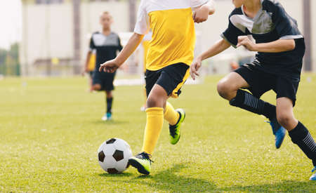 Child kicking soccer ball in a duel. Running footballers compete for the ball. Children attending school soccer tournament game
