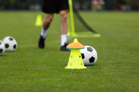 Adult Football Player on Training Unit. Running Footballer on Practice. Soccer Yellow Cone, Training Markers and Soccer Ball in the Foreground. Blurred Grass Field in the Background Stock Photo