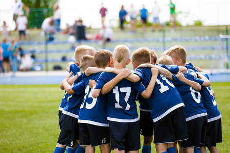 Boys football team forming huddle. Happy kids in a sports team on grass pitch. Summer school soccer tournament. Children playing sports outdoor