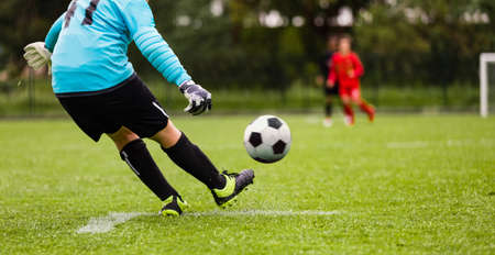 Young Soccer Goalie Kicking Ball. Football Goalkeeper Starts Game Passing Ball to Team Members