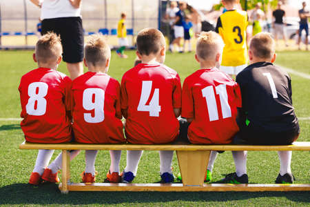 Boys in red shirt sports team. Children sitting on substitute soccer bench. Kids on school football tournament. Soccer coach and competition game in the background