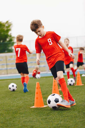 Boys kicking football balls on outdoor training. Group of young soccer players practicing dribbling skills running balls between training cones. Youth soccer team in red jersey shirts