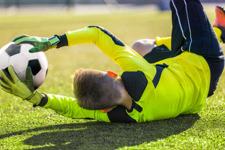 Soccer Goalie Catching Ball. Young Boy Goalkkeeper Saving Goal. Acrobatic Football Goalkeeper Save. Soccer Player in a Goal on a Sunny Summer Day. Soccer Goalie Training Unit