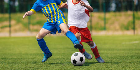 Two Soccer Boys Kicking Ball in Opposite Teams. Young Football Players Running in Duel and Playing Soccer Tournament Match. Sports Competition for Youth Athletes. School Training Pitch in Background