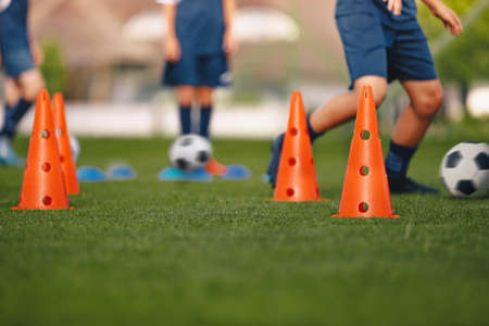 Players dribbling on football venue. Practice unit for football club. Boys running ball on grass training pitch. Red soccer training cones. Football class