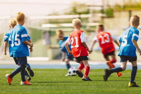 Young Footballers Kicking Football Match.Football Soccer Players Running with Ball. Soccer Players Running After the Ball. Kids in Soccer Red and Blue Uniforms. Soccer Stadium in the Background