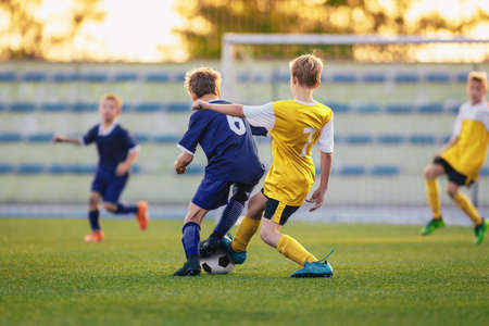 Children Playing Football. Group of Young Boys Kicking Soccer Ball on Stadium Field. Players Compete in Football Match in Two Teams. Kids in Yellow and Blue Soccer Jersey Shirts