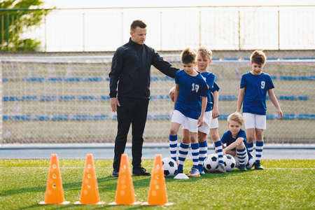 Young Coach With Kids in Soccer Team on Training Unit. Youth Team Coach Training School Boys in Football Soccer. Physical Education for Children Stockfoto