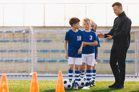 Soccer Coach Motivating Kids on Training. Young Coach With Kids in Soccer Team on Training Unit. Coach on Training with School Boys. Physical Education for Children