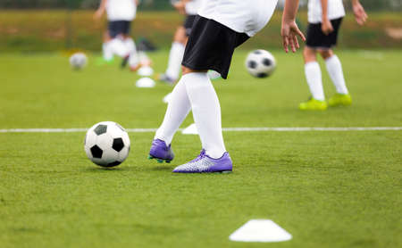 Soccer Player Kicking Ball on Training. Group of Footballers Improving Skills on Practice Venue. Soccer Boy in Purple Cleats and White Soccer Jersey Kit
