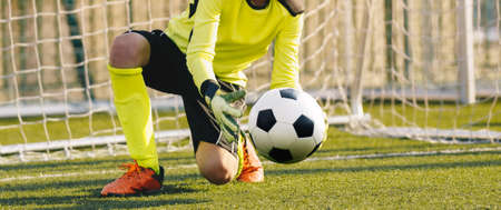 Young Football Galkeeper Catching Soccer Ball. Soccer Goalie in Action Saving Ball in a Goal