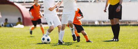 Running Football Players. School Soccer Teams Compete in Tournament Match. Young Football Players and Referee in a Game. Football Stadium in Background