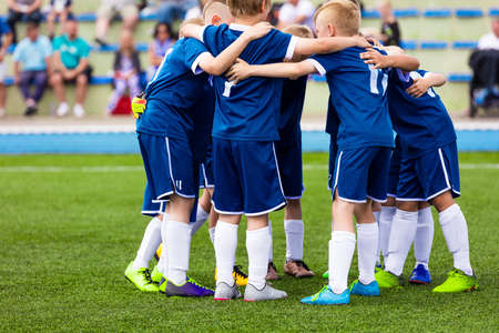Football Team Players Huddling in a Group. Kids Playing Sports and Motivating Before The Game. Children in Blue Soccer Jersey Sportswear. Happy School Kids Stockfoto