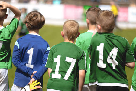Boys in Green Soccer Jersey Shirts Standing in a Team and Watching Football Tournament Match. Kids Playing Sports Outdoor in Summer Sunny Day