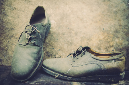 modes: still life with boots on wooden table over grunge background