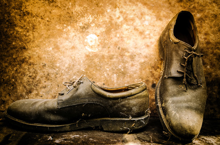 senile: still life with boots on wooden table over grunge background
