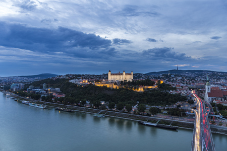Bratislava castle city view at night, bridge with the Dome and Danube river, city lights trails