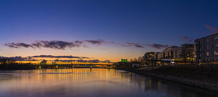 View from harbour at sunset, Bratislava castle, business buildings and river Danube, Slovakia