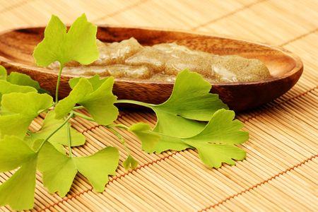 body scrub: bowl of body scrub with ginko leaves - beauty treatment
