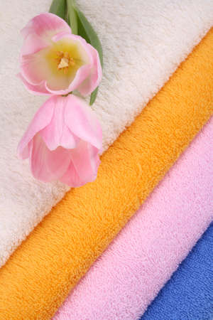 closeups: stack of clean colorful towels with tulips close-ups