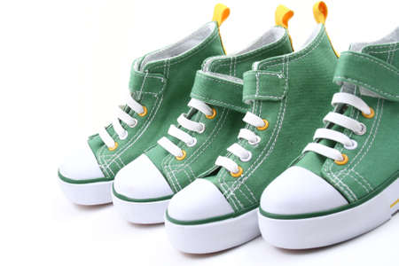 two pairs of green sneakers for children isolated on white photo