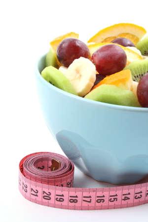 fruit salad: bowl full of delicious fruit salad - kiwi banana orange and grapes - isolated on white