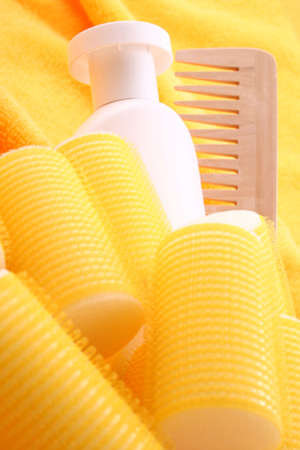 hair care - curlers shampoo and comb on yellow towel